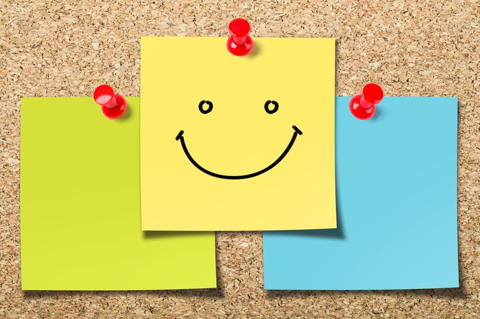 A cork board with smiley post-it notes.