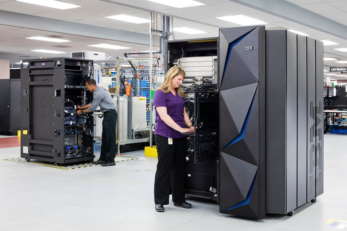 A woman standing next to an IBM Z Mainframe, typing on a keyboard.