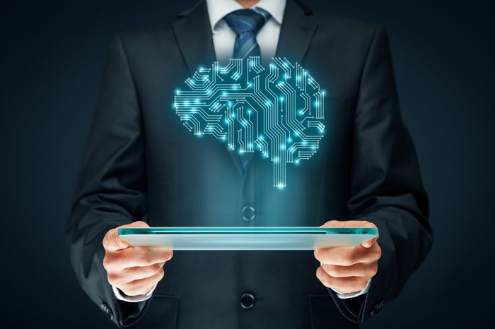 A man in a suit is holding a computer. A brain-shaped illustration of electronic connections depicting artificial intelligence hovers above the screen.