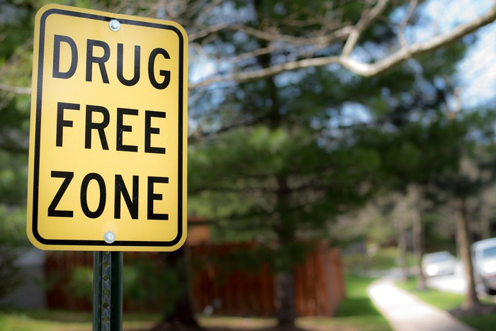 A yellow drug-free zone sign in a quiet neighborhood.