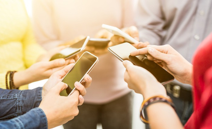 A group of people use smartphones.