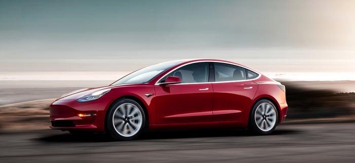 A red Tesla Model 3, a sleek compact luxury sedan, on a coastal road at sunset.