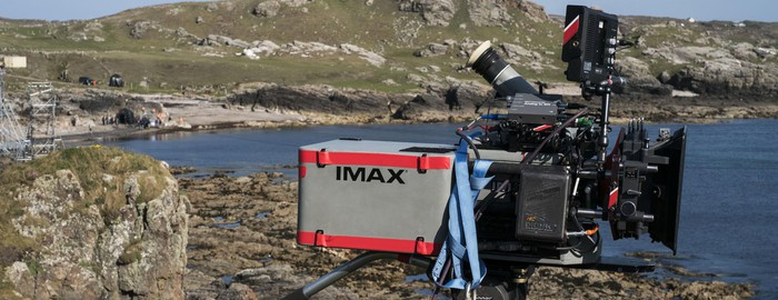 An IMAX high-resolution movie camera set up on the rocky shore of a lake.