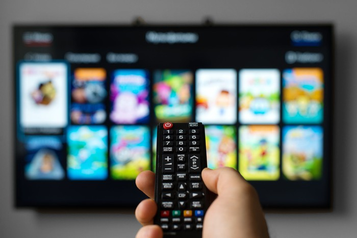 A man controls a smart TV with a remote.