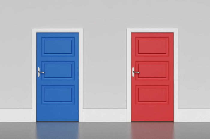 A wall with a blue door on the left and a red door on the right.