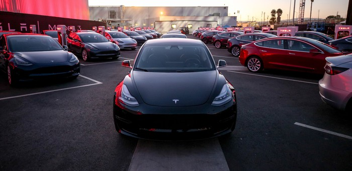 A black Tesla Model 3 parked between two rows of other Model 3 cars.
