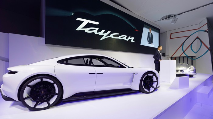 Blume is standing on an auto-show stage with the Taycan, a sleek white sports sedan, and a vintage Porsche sports car.