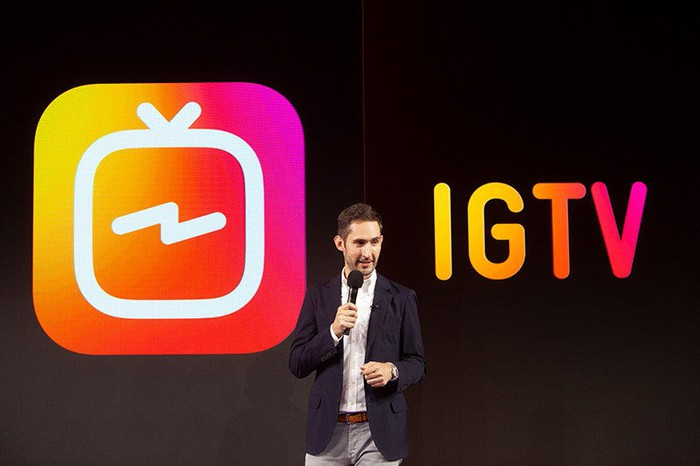 Instagram CEO Kevin Systrom is on stage announcing IGTV with the IGTV logo on the screen behind him.