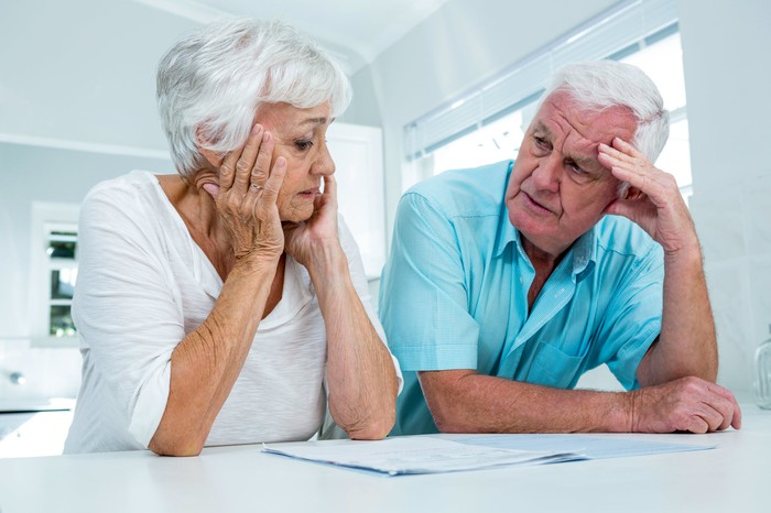Senior couple reviewing documents with concerned expressions