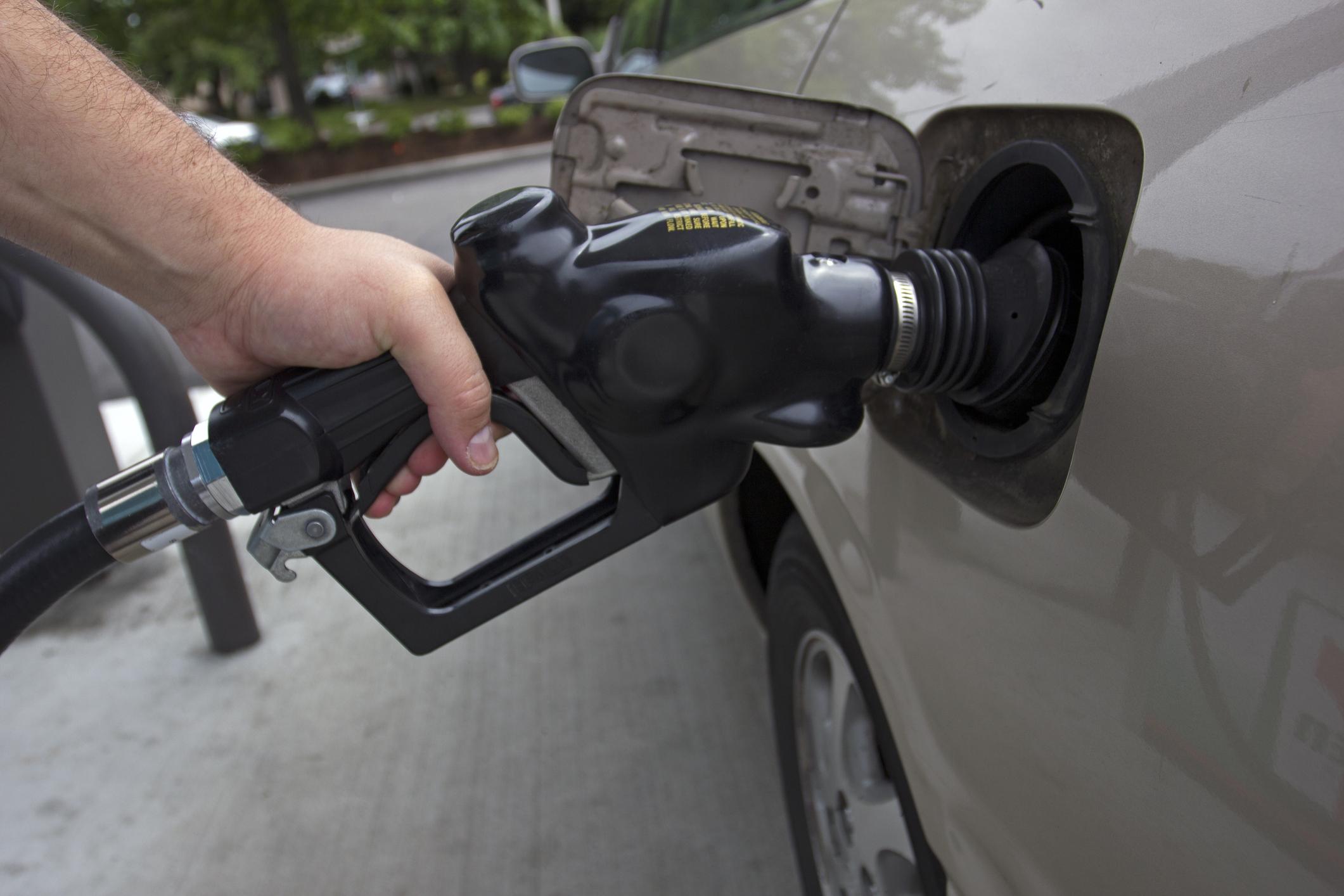 A person pumping gas into their car.