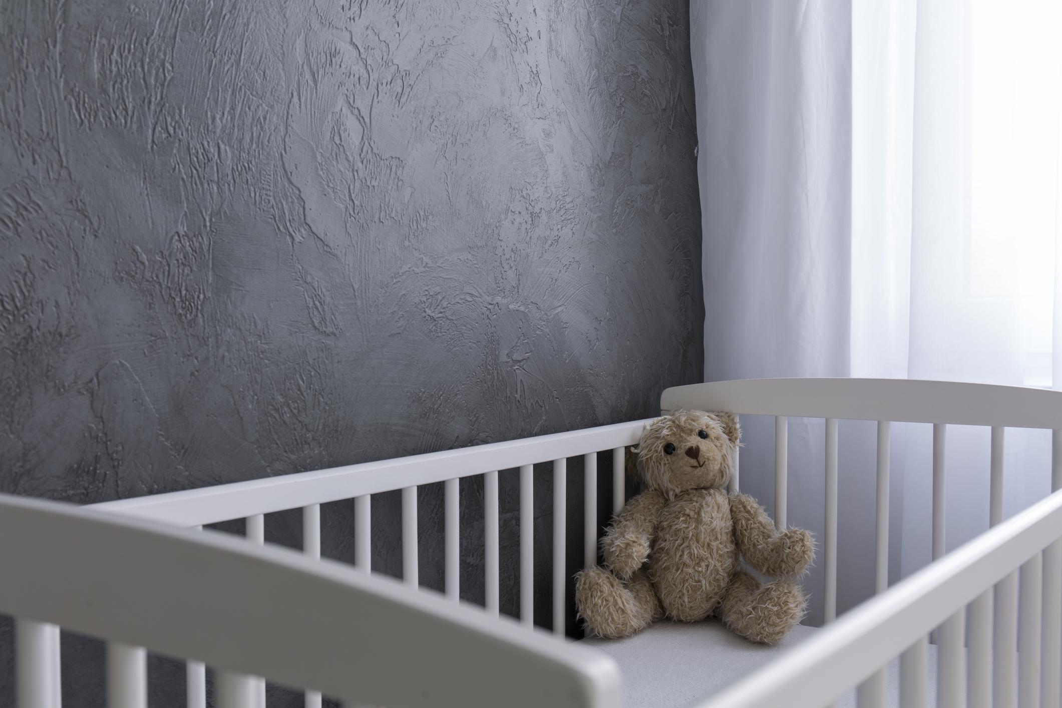 An empty crib with a stuffed animal bear lying in the corner.