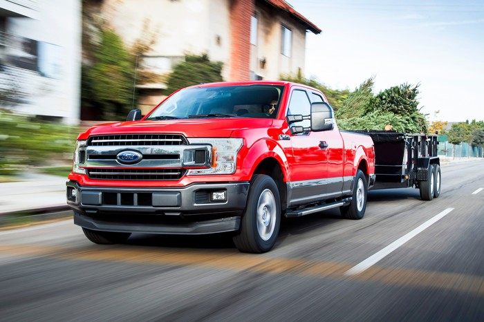 A red 2018 Ford F-150 pulling a trailer.