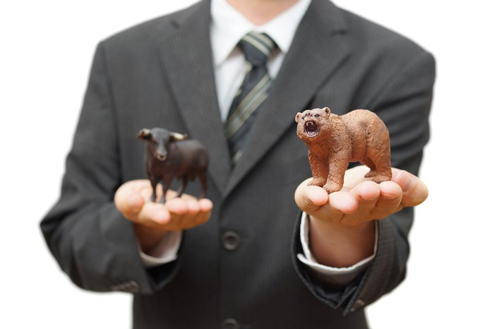 A man in a business suit holds a bear and bull figurine in each hand.