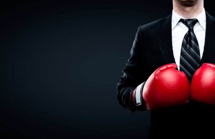 A man wearing a suit and tie and boxing gloves.
