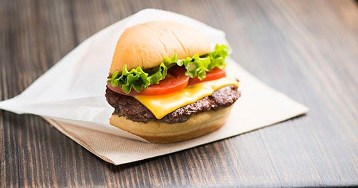 Shake Shack cheeseburger with tomato and lettuce tucked into a waxed paper bag, sitting on a napkin