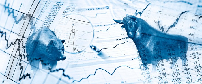 Bear and bull of the stock market depicted on a page of ticker prices.