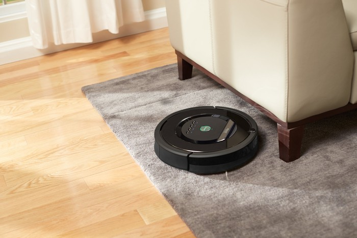iRobot Roomba cleaning a carpet next to a couch