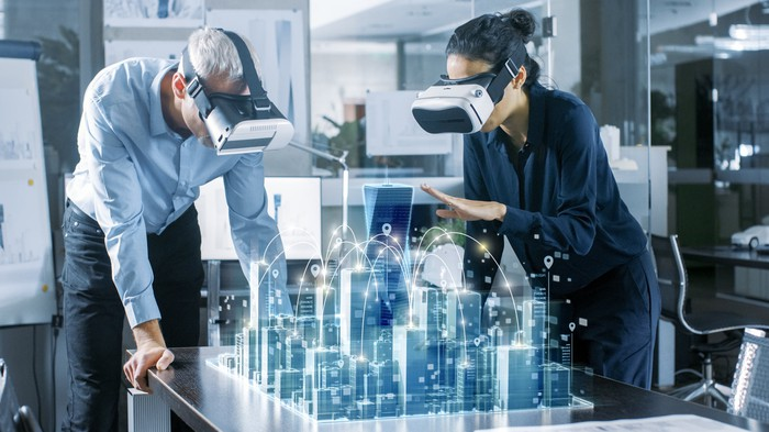 A man and a woman view AR models of buildings with headsets.