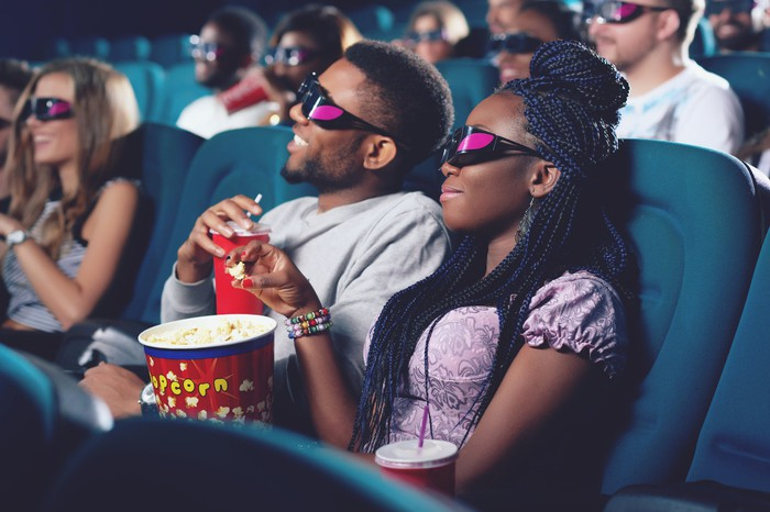 A couple in a movie theater wearing 3D glasses and eating popcorn