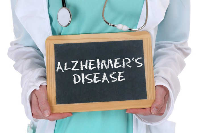 """Physician holding small chalkboard with """"Alzheimer's disease"""" written on it"""