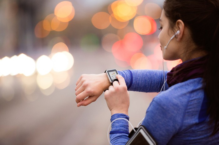 A jogger interacts with her smartwatch.