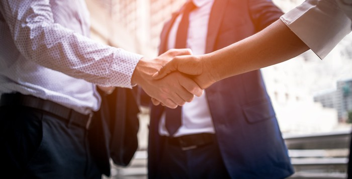 Two people in business attire shaking hands