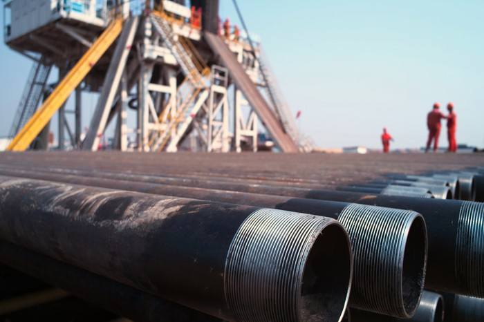 A close-up of drill pipes with oil workers and a rig in the background.
