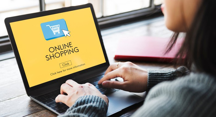 """Woman sitting in front of a laptop computer with the words """"online shopping"""" displayed."""