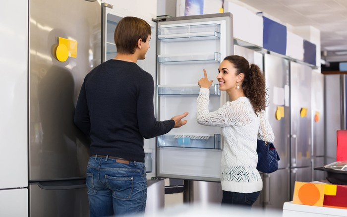 Man and woman looking at refrigerators in a store.