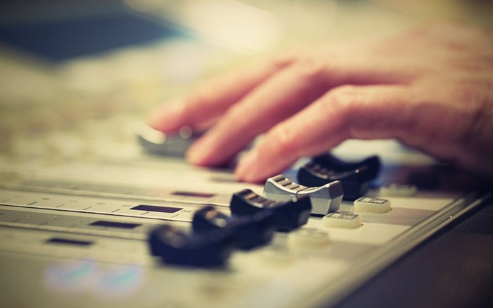 A DJ adjusts controls on a mixer.