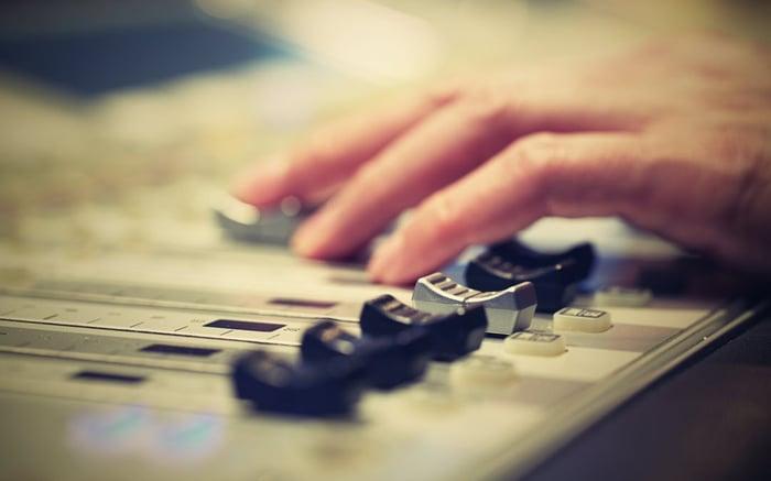 A DJ adjusts controls on a mixer.