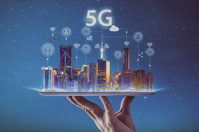 Hand holding up a city connected with 5G