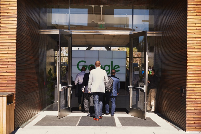 Several well-dressed people walking into an open door with the Google logo prominently displayed.