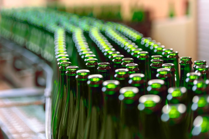 Rows of manufactured green glass bottles on an assembly line.