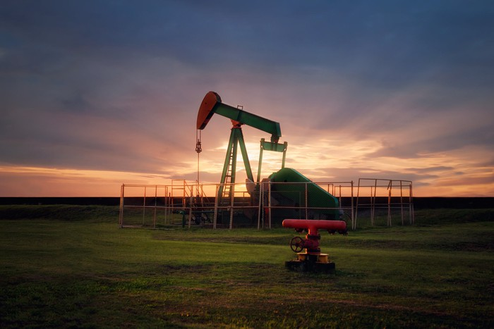 An oil pump in a green field with the sun setting in the background.