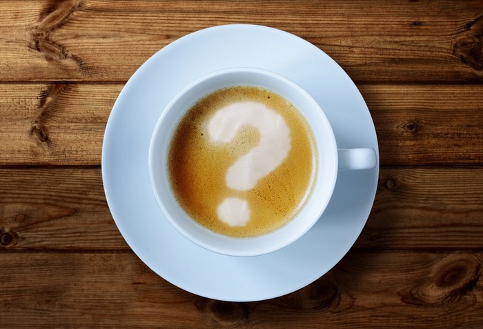 An overhead view of a coffee cup with a question mark in the froth.