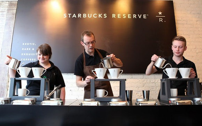 Baristas making coffee at Starbucks Reserve bar.