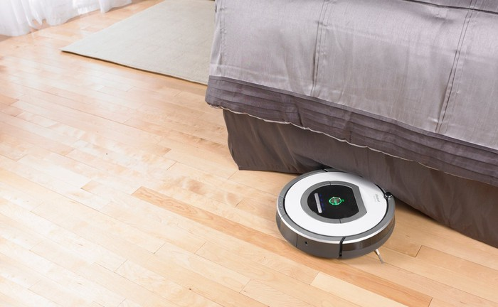 The iRobot Roomba 700 Series robotic vacuum cleaning around the edge of a bed.