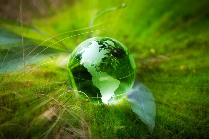A green globe sitting on the grass.