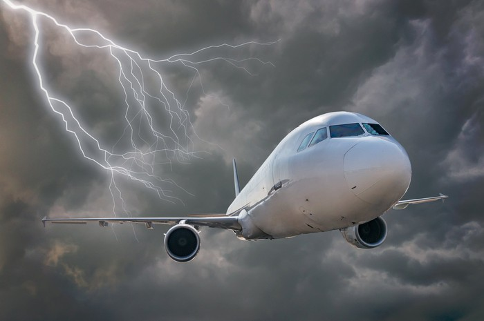 White passenger airplane flying through dark storm clouds and lightning strikes.