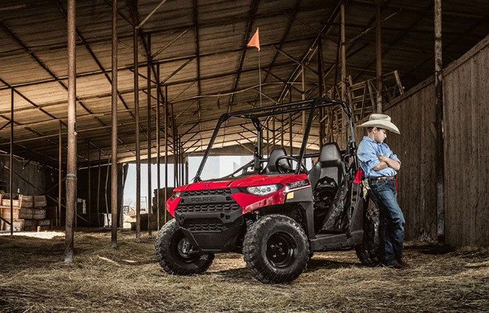 Younger farmer standing beside a Polaris Ranger