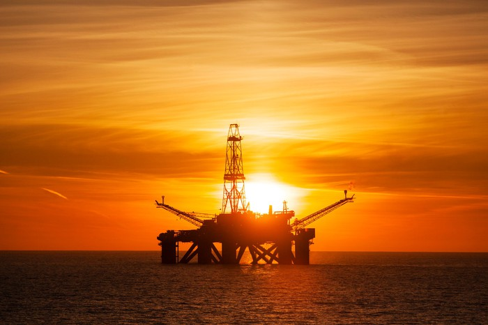 An offshore driling rig with the sun setting in the background.