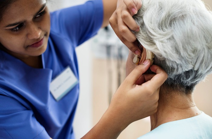 Technician helping adjust a hearing aid in a woman's ear