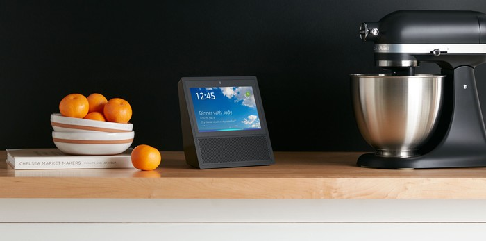 Echo Show on a counter, next to a bowl of fruit and a stand mixer
