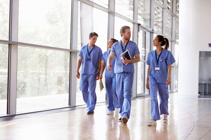 Four medical professionals in blue scrubs walk down a hallway.
