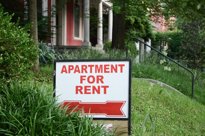 An apartment for rent sign posted in front of a building