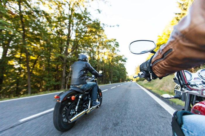 Two people riding motorcycle down the road.