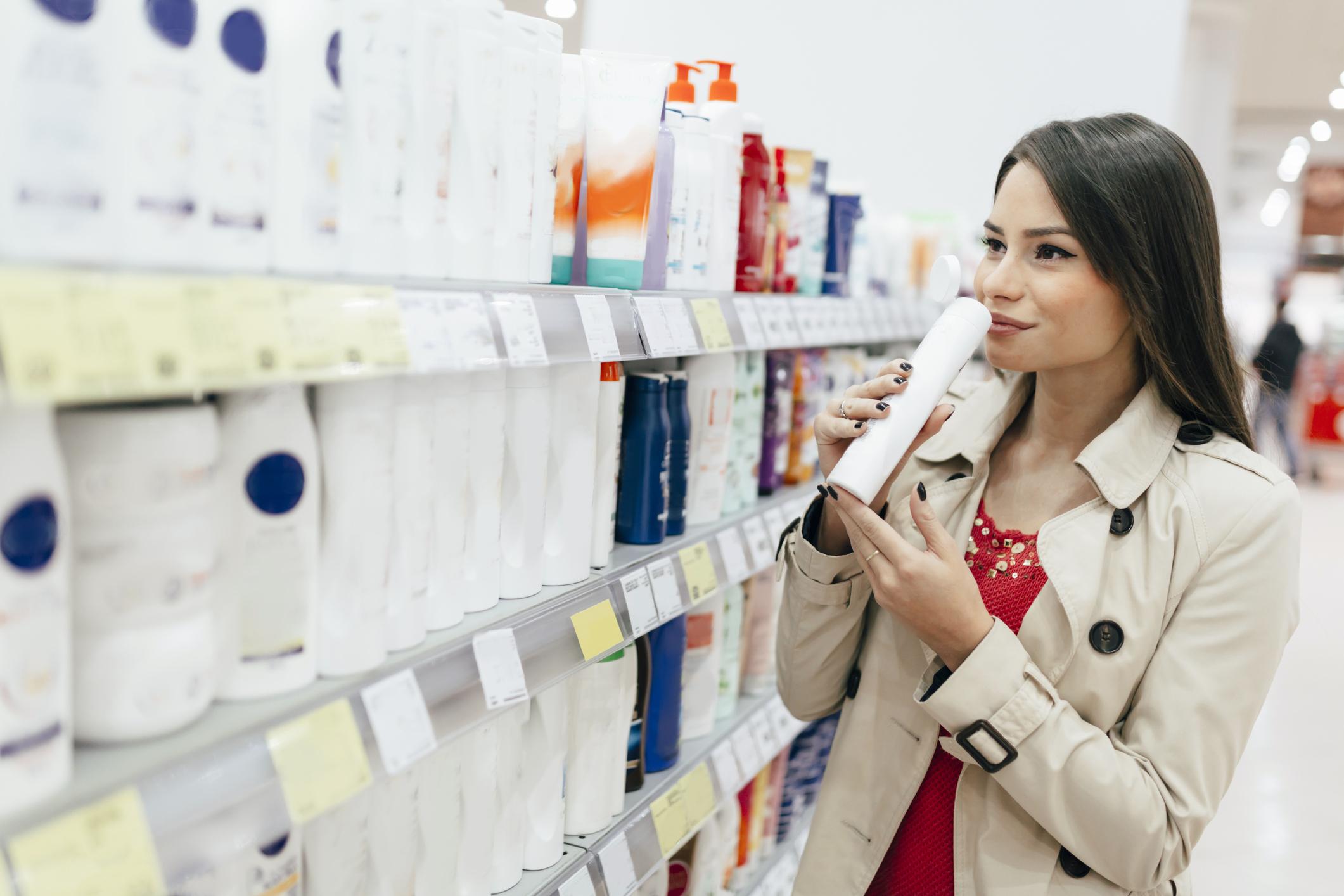A woman shops in the shampoo aisle.