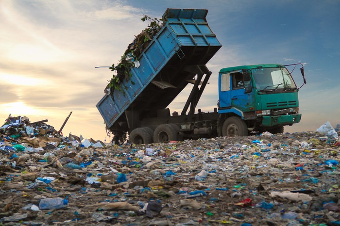 A garbage truck dumping a load at a landfill.