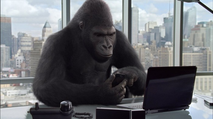 A gorilla at a desk, using a smartphone and laptop